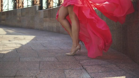 Sexy Female Legs in High-heeled Shoes. The Girl in the Evening Dress Is Walking Down the Street