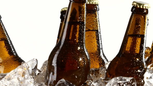 Drunk Beer in Dark Bottles Stands in the Ice. White Background.