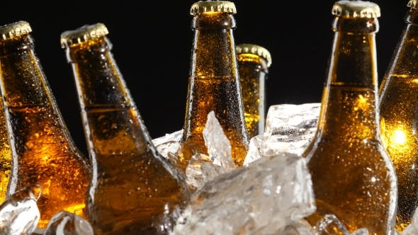 Thumbnail for Condensate Flows Down the Brown Glass of Bottles From Beer. Black Background.