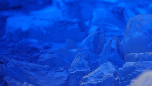Thumbnail for Pieces of Ice Lies on the Table, Blue Illumination Beautifully Lies Over Fragments.