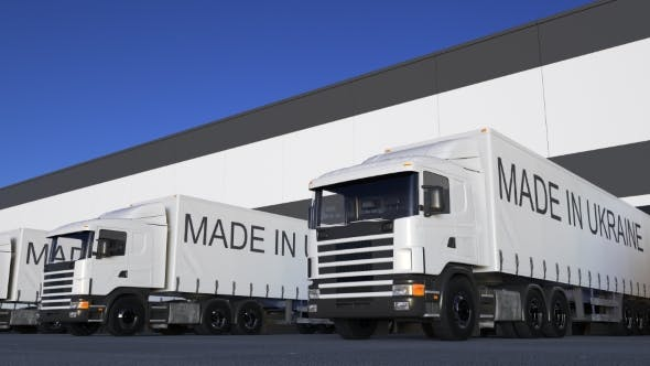 Thumbnail for Freight Semi Trucks with MADE IN UKRAINE Caption on the Trailer Loading or Unloading