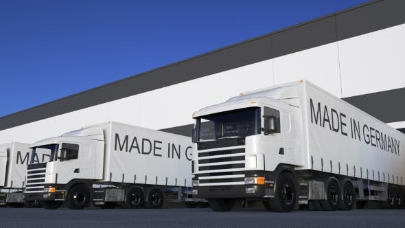Thumbnail for Freight Semi Trucks with MADE IN GERMANY Caption on the Trailer Loading or Unloading