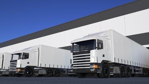 White Freight Semi Trucks Loading or Unloading