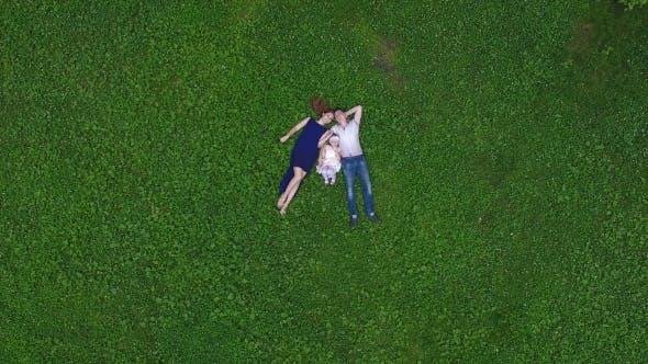Thumbnail for Glückliche Familie liegend auf Gras und Blick auf die Kamera im Park