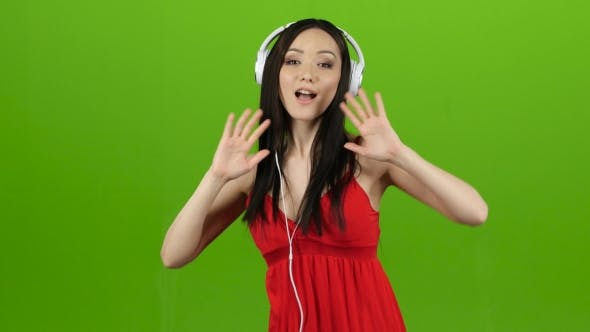 Thumbnail for Girl Listens To Cheerful and Energetic Music Through Headphones. Green Screen