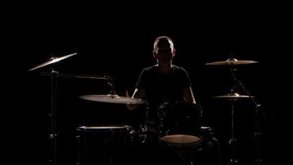 Thumbnail for Musician Plays Professionally Good Music on Drums Using Sticks. Black Background. Silhouette