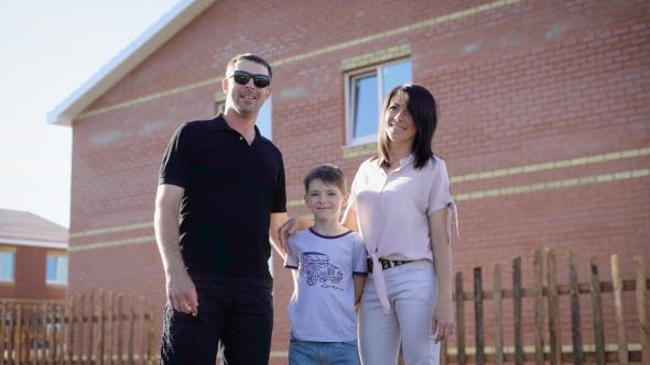 Thumbnail for Image of Happy Family Dressed in Casual Clothes Standing Near Their New House in Sunny Summer Day