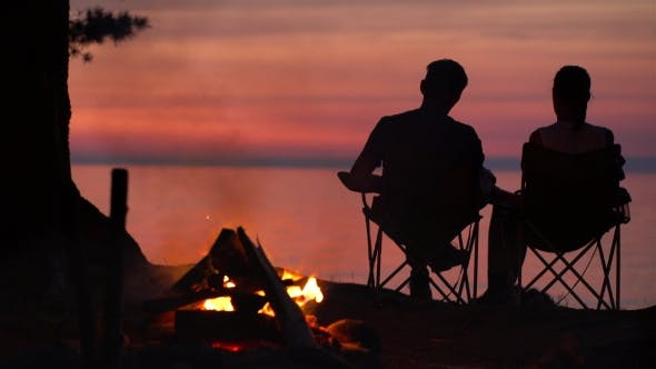 Thumbnail for Couple Is Sitting Near Campfire at Night.
