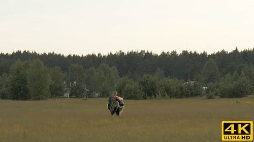 Paratrooper Goes with Folded Parachute After Landing