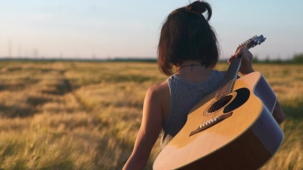 Thumbnail for Girl Walking Alone with a Guitar at Wheat Field