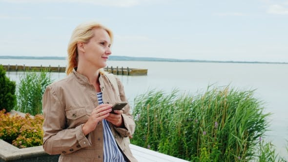 Thumbnail for A Young Woman Is Walking Around the Lake, Using a Mobile Phone. Lake Balaton in Hungary