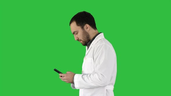 Cover Image for Walking doctor or nurse texting on a cell phone on a Green