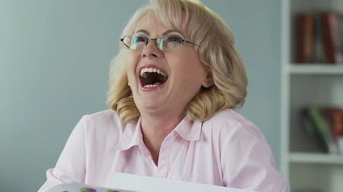 Cheerful Mature Woman Winning Lottery, Laughing and Rejoicing Money Prize
