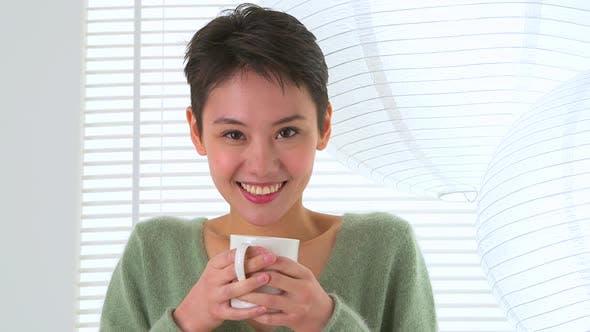 Happy Asian woman drinking tea