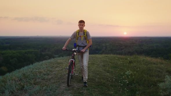 Cover Image for A Tired Teenager with a Biker Behind His Back Drives His Bicycle Along the Rural Road