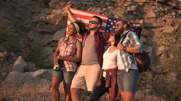 Thumbnail for Excited Friends Posing Among Rocks with Flag