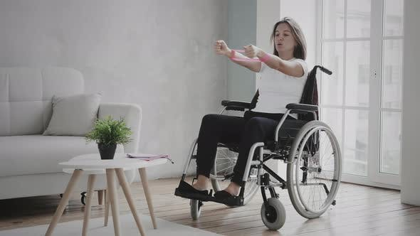 Thumbnail for Woman in wheelchair is exercising at home