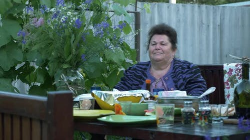 Elderly mature woman sits at dining table in courtyard. Family time at picnic.