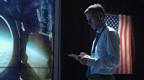 Man with Tablet in Mission Control Center. Elements of This Image Furnished By NASA.