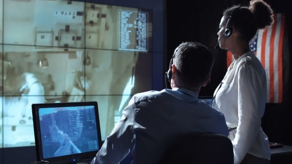 Scientists in Flight Control Center. Elements of This Image Furnished By NASA.