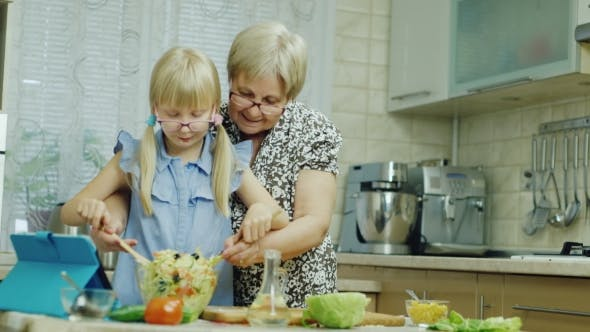 Thumbnail for Girl of 6 Years Together with the Grandmother Do a Salad in Kitchen