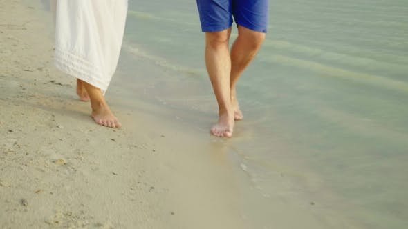Cover Image for Bare Feet of a Man and a Woman Walk Along the Sand Along the Sea. Holiday Together in the Tropics