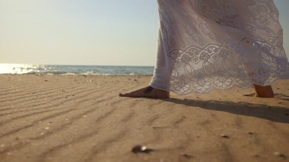 Thumbnail for Legs of Caucasian Girl Wearing White Long Dress and Silver Bracelets Walking Barefoot Sand on Sea