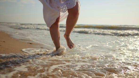 Thumbnail for Legs of Caucasian Girl Wearing White Long Dress and Silver Bracelets Walking Barefoot Sand on Sea