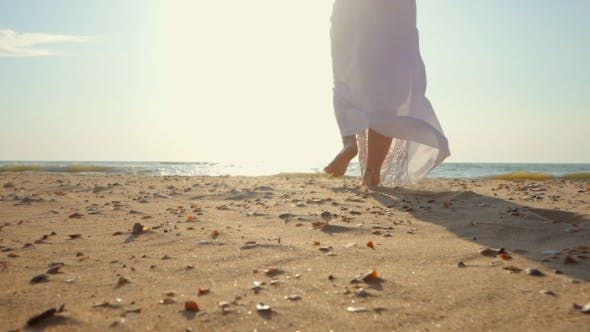 Legs of Caucasian Girl Wearing White Long Dress and Silver Bracelets Walking Barefoot Sand on Sea