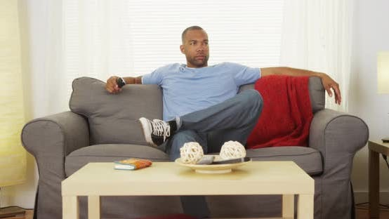 Thumbnail for Black man sitting on couch watching tv