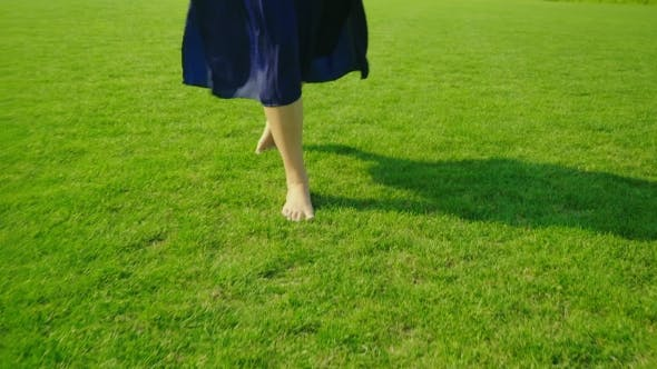 Thumbnail for Barefooted Female Legs Walking on Green Grass
