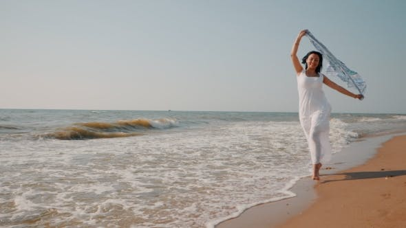 Thumbnail for Gypsy Young Brunette Girl Wearing White Maxi Long Dress Running Near Sea or Ocean Windy Beach with