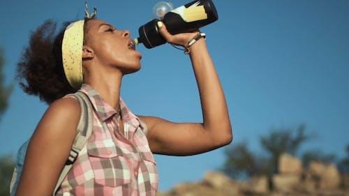 Thirsty Girl Drinking Water While Trekking