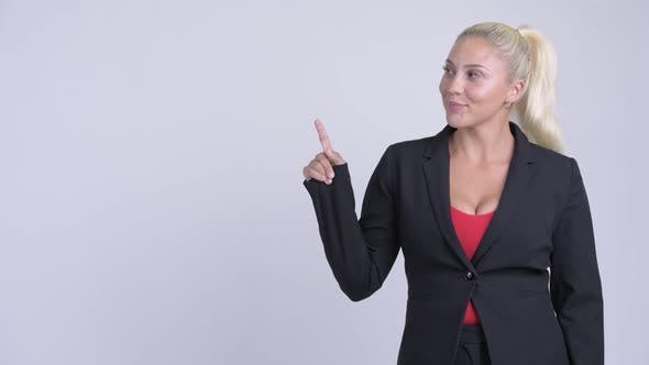 Cover Image for Young Happy Blonde Businesswoman Thinking and Pointing Up