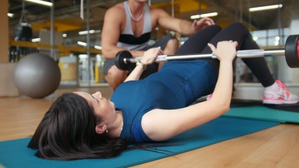 Cover Image for Slim Young Women Doing Exercise for Buttocks - the Rise of a Body Lying Over the Bar