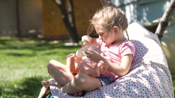 Thumbnail for Girl Playing with Baby Doll in Backyard