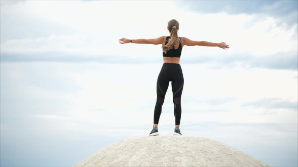 Thumbnail for Woman Doing a Breathing Exercise Standing on Stone, She Looks Into the Distance