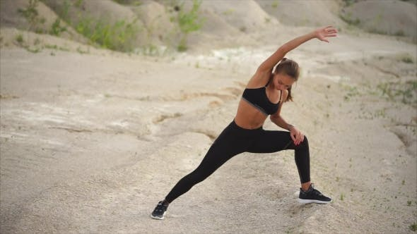Athlete Does Stretching the Muscles of the Body and Thighs in the Nature