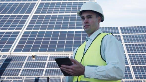 Thumbnail for Solar Panel Technician Using Tablet Near Array