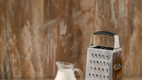 Thumbnail for Close Up of Grated Cheese and Jug of Milk on Table 45