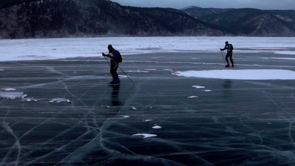 Thumbnail for Two Men Are Skating on the Ice of Frozen Lake Baikal During Beautiful Sunset.