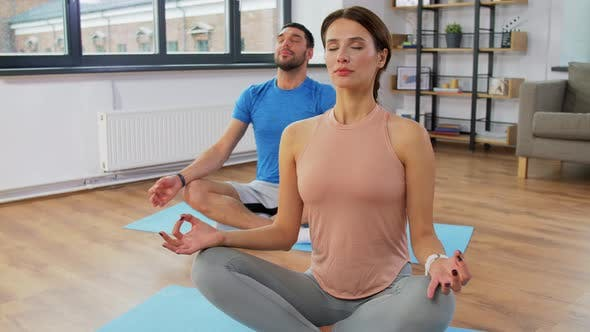 Thumbnail for Happy Couple Meditating in Yoga Lotus Pose at Home