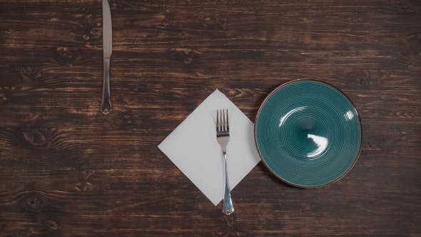 Thumbnail for A Green Plate Moves on the Table with Cutlery
