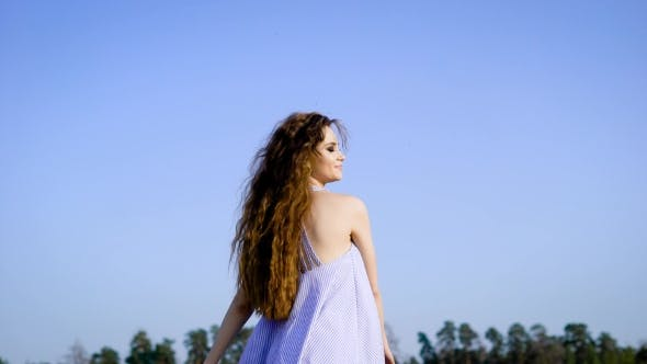 Thumbnail for A Happy and Young Woman Enjoys a Summer Day Outdoors, She Waves Her Hands To the Sides