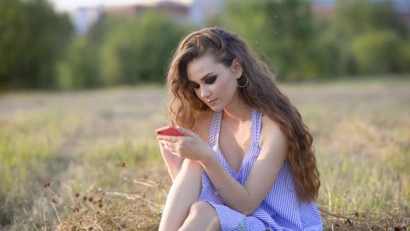 Thumbnail for a Romantic Woman with Smoky Eyes and Curly Hair Writes a Message on Her Mobile Phone