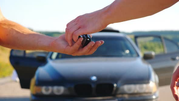 Thumbnail for Unrecognizable Man Getting Car Key From Seller. Male Hands Giving Keys of Car To His Friend Outdoor