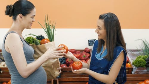 Saleswoman Helps To Choose a Tomato