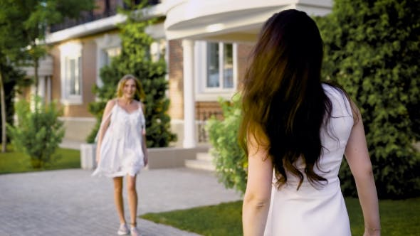 Thumbnail for Two Friends in Stylish Dresses Meet on the Street on a Summer Day, the Girls Are Glad To Each Other