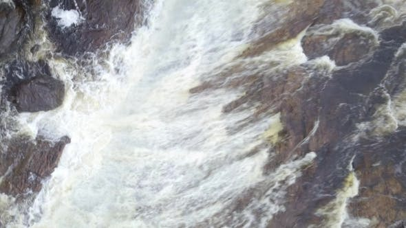 Thumbnail for Rising Aerial Shot Looking Down at Raging Waterfall in a River