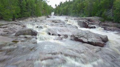 Low Level Aerial Drone Shot of Raging River in a Forest